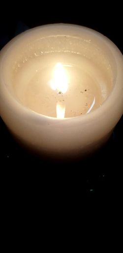 Close-up of lit tea light candle in darkroom