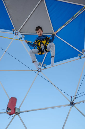 Low angle view of boy bungee jumping at trampoline