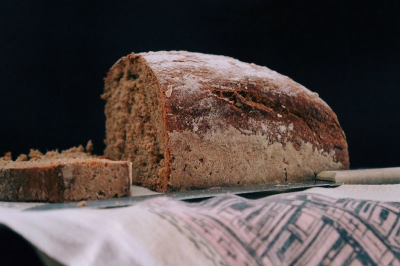 Close-up of bread with knife on table against black background