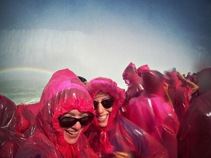 Happy people in pink raincoats at horseshoe falls