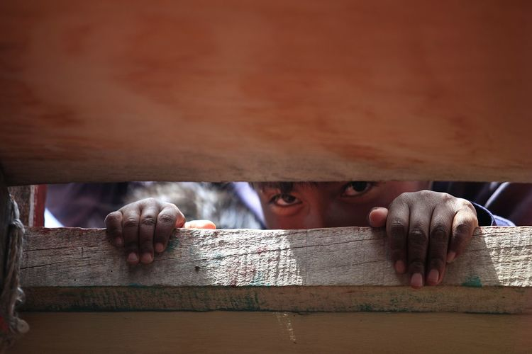 Close-up portrait of boy peeking through wooden bamboo