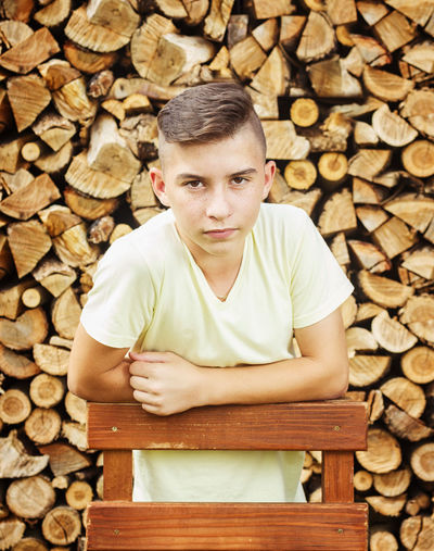 serious boy in front of log of wood Arms Crossed Childhood Firewood Log Looking At Camera Nature One Person Pile Portrait Serious Seriousface Stack Standing Teenage Boy Timber Wood - Material Wooden Chair Woodpile