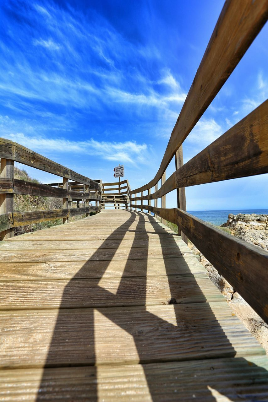 shadow, sunlight, bridge - man made structure, sky, day, pier, wood - material, built structure, outdoors, connection, cloud - sky, architecture, nature, sea, water, footbridge, blue, scenics, beach, wood paneling, no people, beauty in nature, underneath