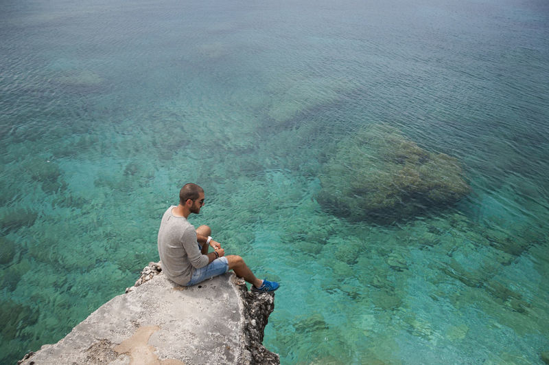 High angle view of mid adult man looking at sea while sitting on rock