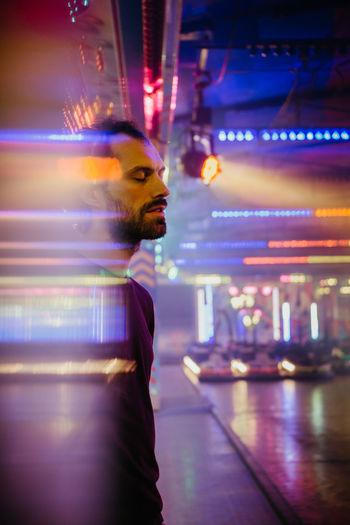 Side view of man standing at illuminated nightclub