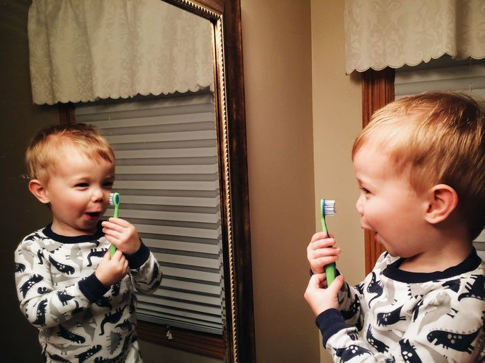 Boy holding toothbrush in front of mirror