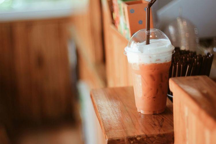 Thai milk tea on wooden table