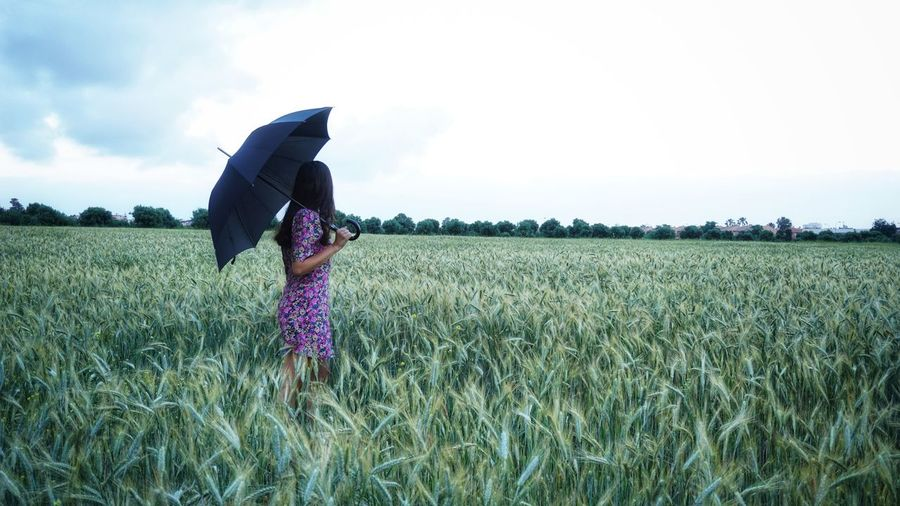 Woman standing in field with a parasol