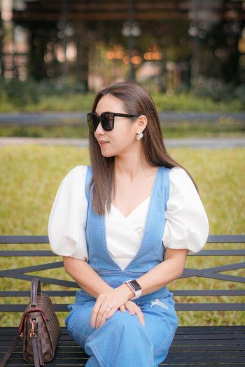 Beautiful woman wearing sunglasses sitting on bench at park