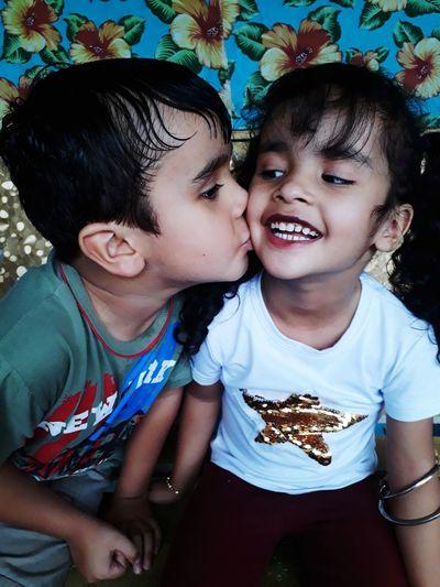 Boy kissing sister