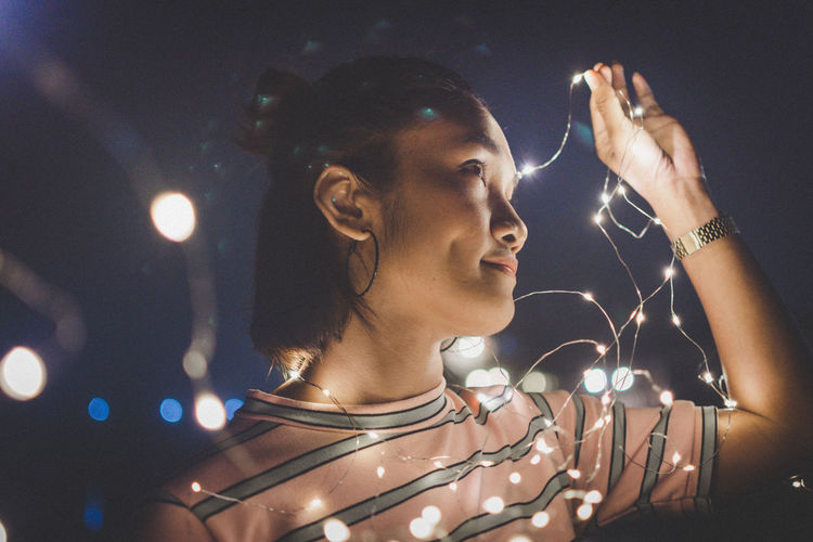 Close-up of smiling young woman with illuminated string lights in city at night