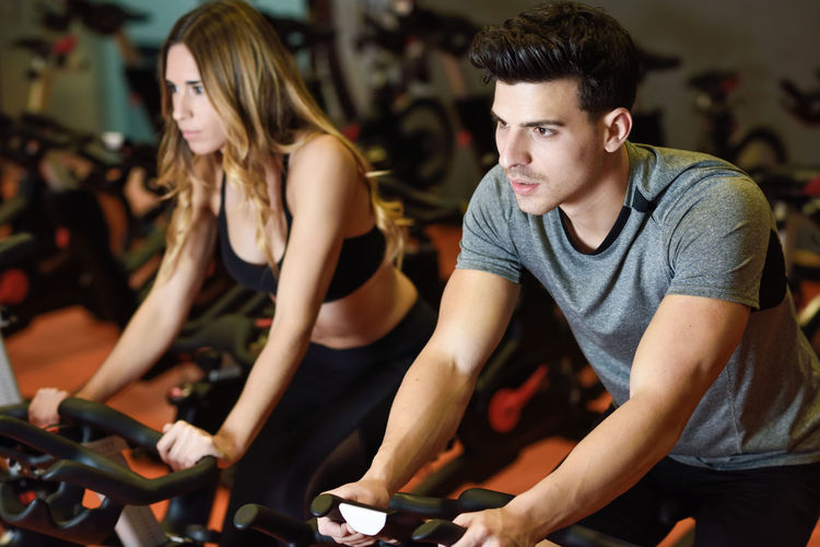 Young man and woman biking in the gym, exercising legs doing cardio workout cycling bikes. Two people in a spinning class wearing sportswear. Couple Cyclo Exercising Young Adult Cardio Cardio Excercise Cycling Cyclo Indoors Gym Healthy Lifestyle Indoors  Leisure Activity Lifestyles People Sitting Spinning Sports Sports Clothing Young Adult Young People Young Women