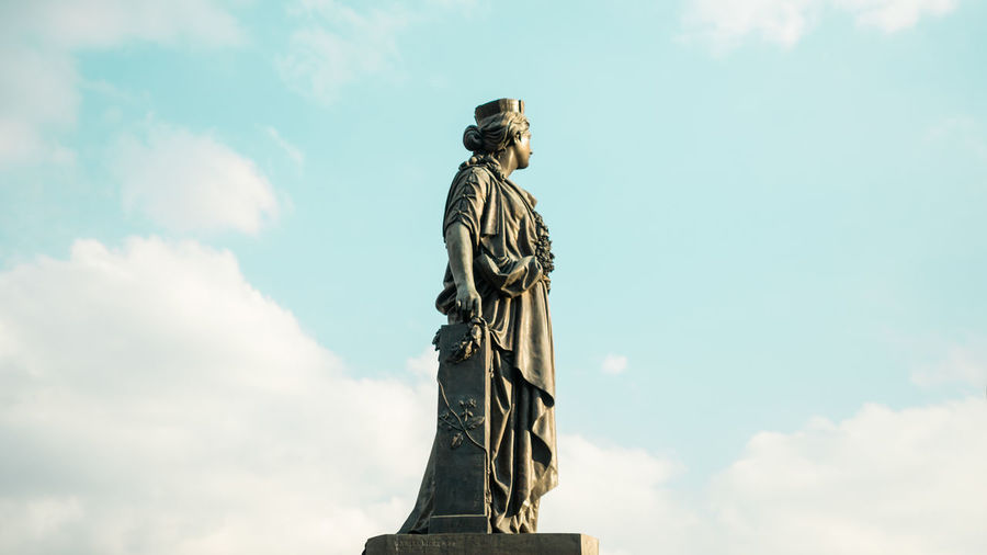 Low angle view of female monument against sky