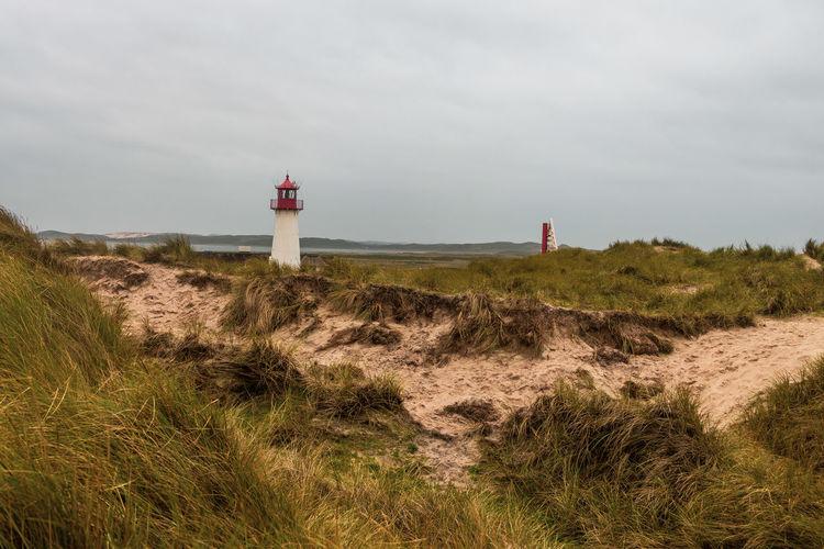 Lighthouse on road amidst buildings against sky
