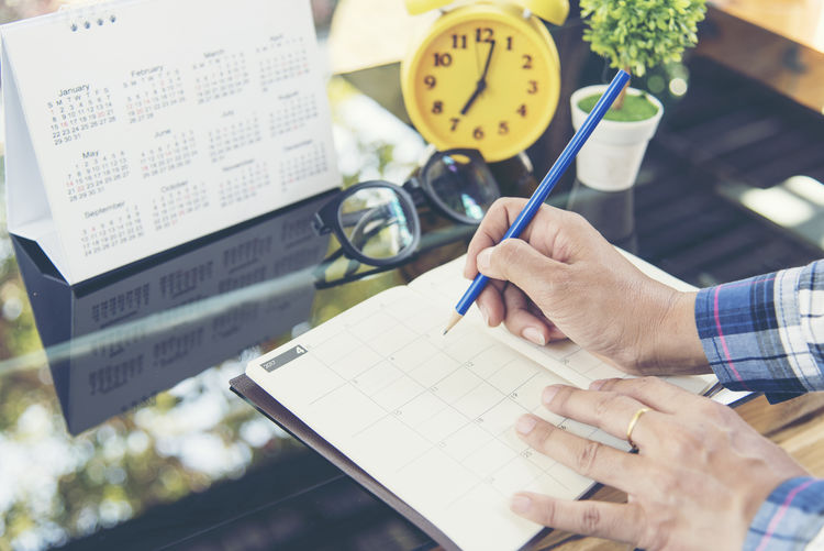 High angle view of businessman writing in diary at office