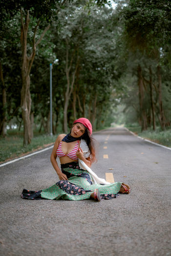 Woman sitting on road by trees in city