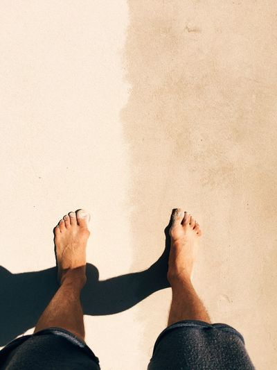 Low section of man standing on sand during sunny day