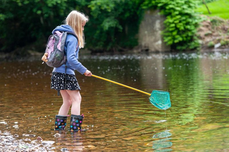 Girl standing against lake