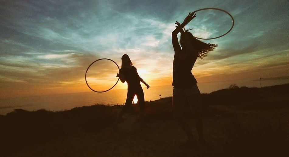 Women playing with plastic hoop on field against sky during sunset