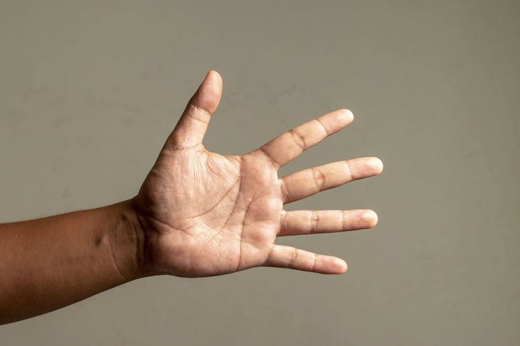 Close-up of hands over human hand against gray background