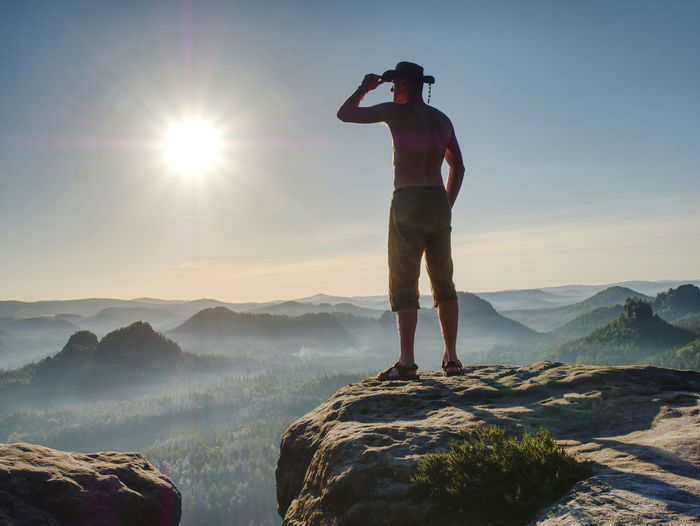 Cowboy style hiker man on cliff watching over misty morning valley to sun. man body with akimbo arms
