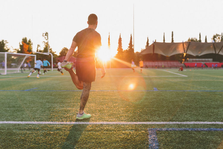 Rear view of man playing soccer on field during sunset