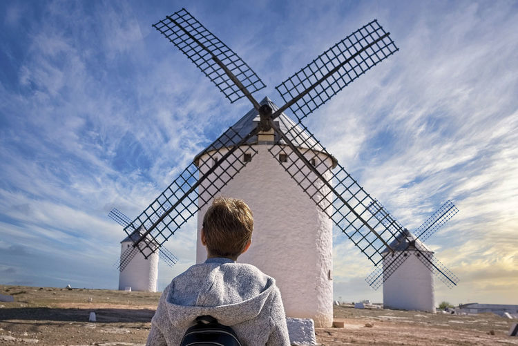 Rear view of mature woman looking at traditional windmills against cloudy sky