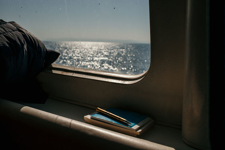 Close-up of books with pen by window in ship