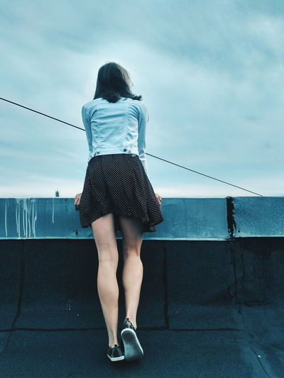 Rear view full length of young woman standing on building terrace against sky