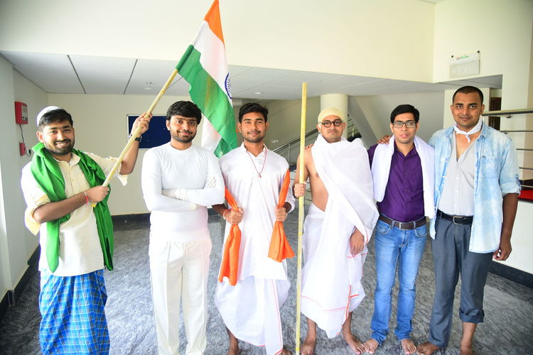 Portrait of friends standing with indian flag on floor