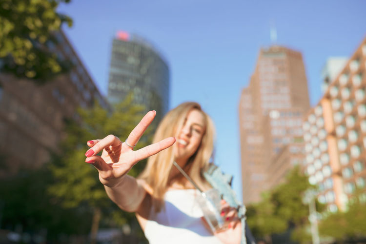 Portrait of smiling woman showing peace sign against buildings in city