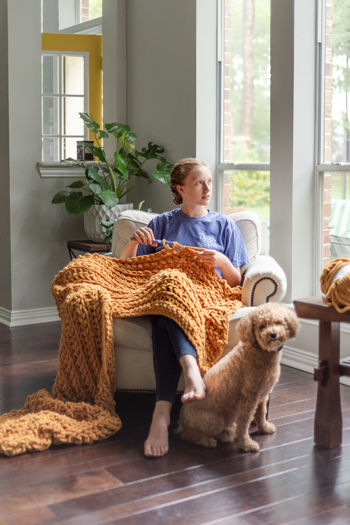 Woman with dog sitting on floor at home
