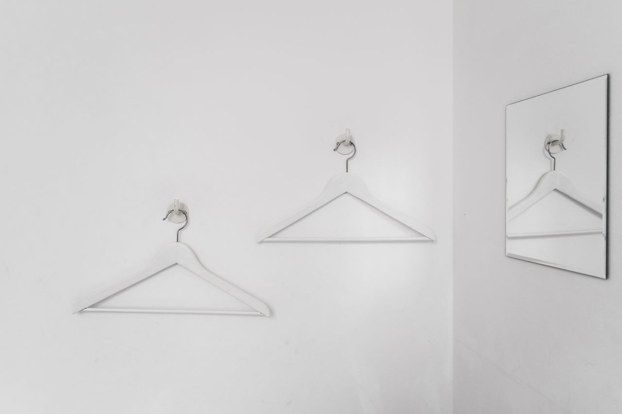 Coathangers Hanging From Hooks Mounted On White Wall