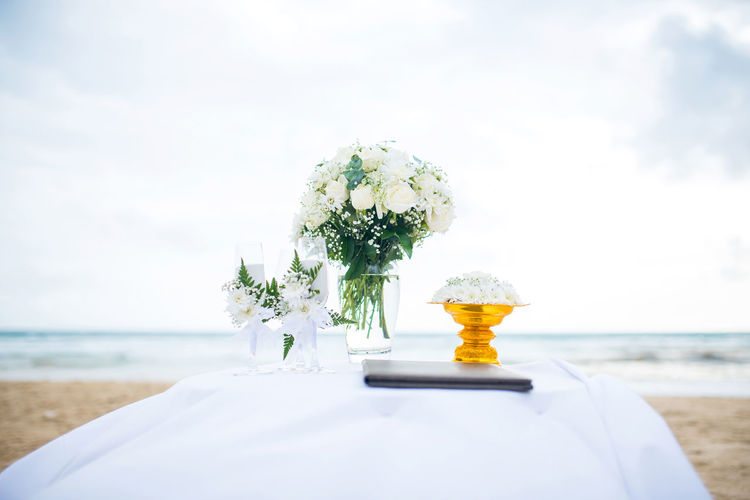 Close-up of white flowers and wineglasses on table at beach