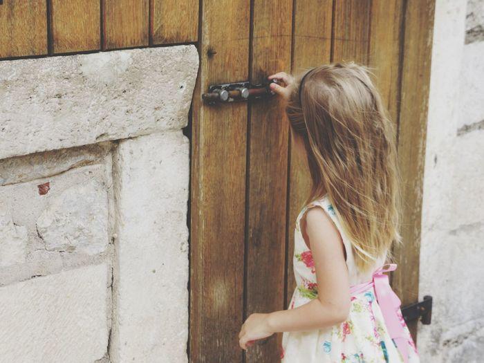 Girl closing door of house