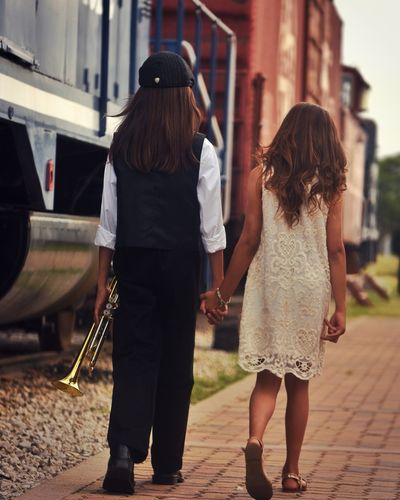 Rear View Of Boy And Girl Walking Holding Hands