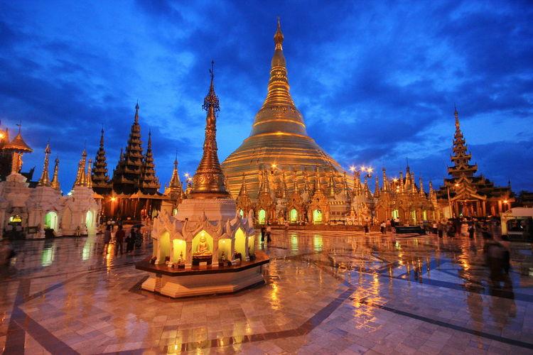 Illuminated temple building against sky at dusk