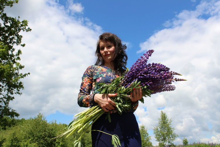 Low angle view of portrait woman holding lavenders while standing against cloudy sky