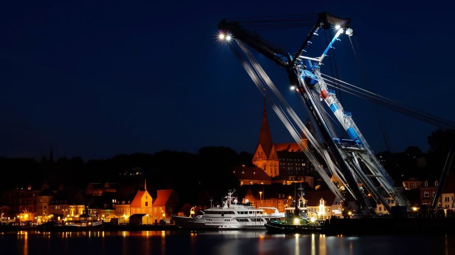 Illuminated shipping cranes at dock by town against sky