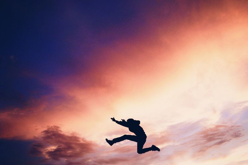 Side View Of Silhouette Person Jumping In Mid-Air Against Orange Sky