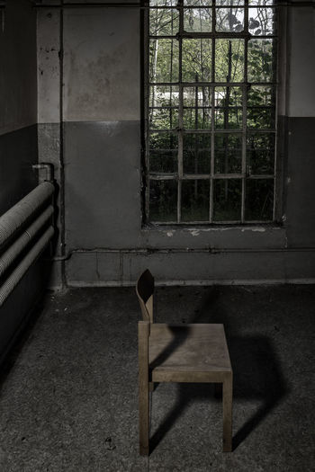Chair In Prison Cell Against Window