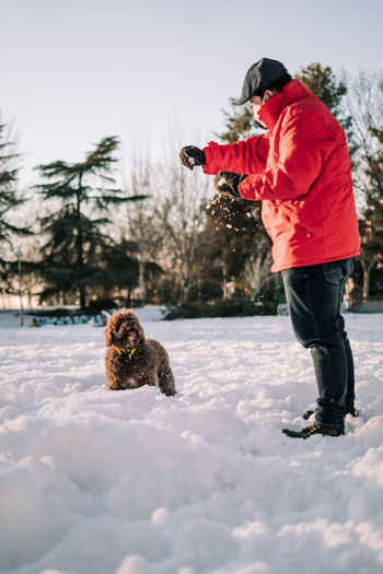 Full length of dog on snow covered field