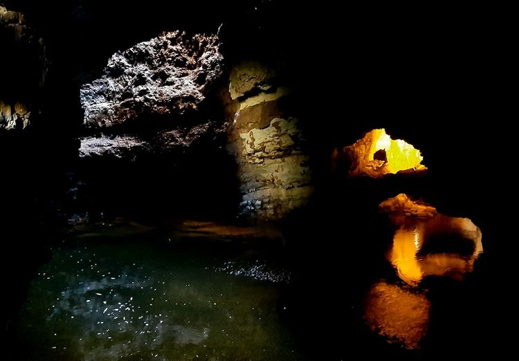 View of illuminated rock formation in water at night