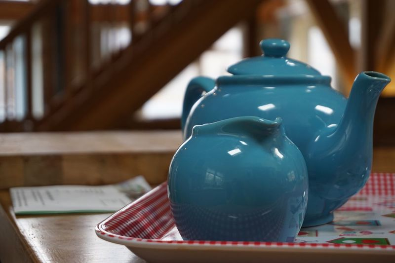 Close-up of blue teapot and container on table