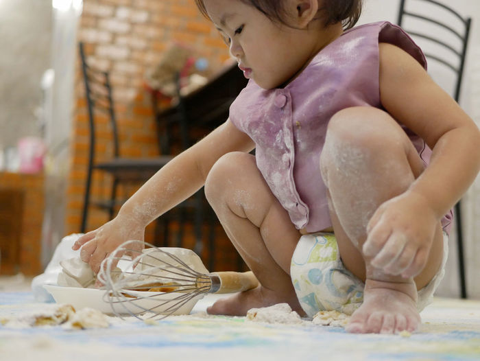 Baby preparing food while sitting on floor
