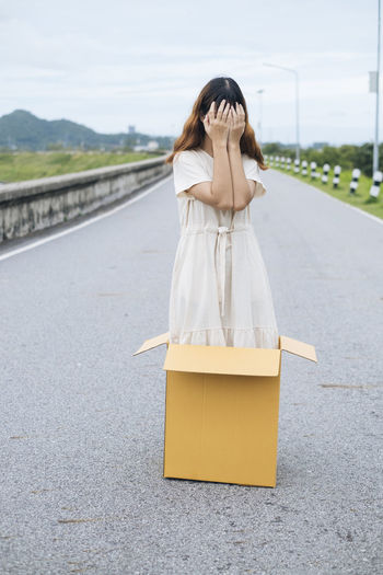 Full length of woman covering face standing in cardboard box on road
