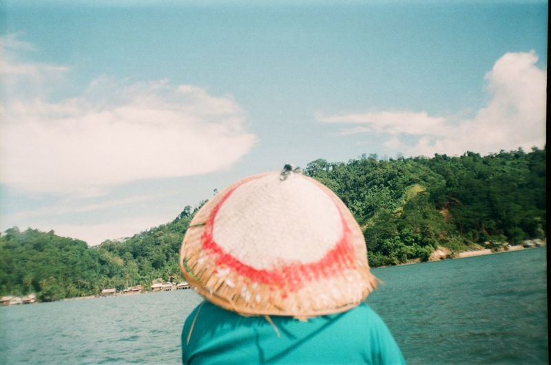 Rear view of woman in hat by lake against sky