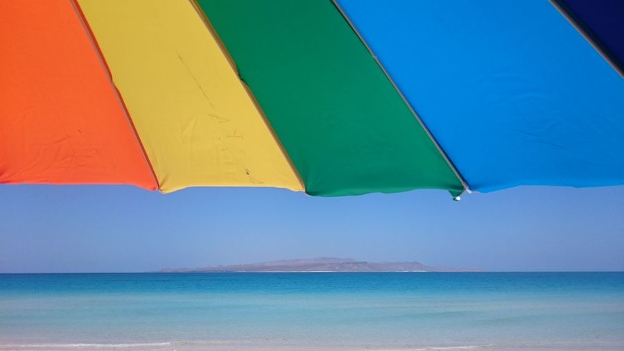 Multi colored parasol by sea against sky