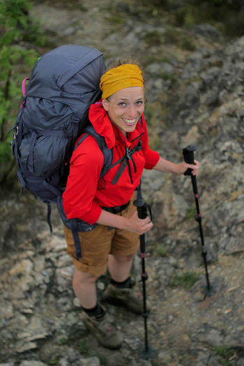 portrait of a caucasian female hiker standing on the rock with backpack Alpine Backpacking Boots Camping Expedition Freedom Hiking Nature Travel Trekking Woman Youth Activity Adventure Backpack Caucasian Climbing Clothing Day Female Full Length Girl Hiking Hobby Holding Leisure Activity Lifestyles Mountain Nature One Person Outdoors People Real People Sport Walking Women