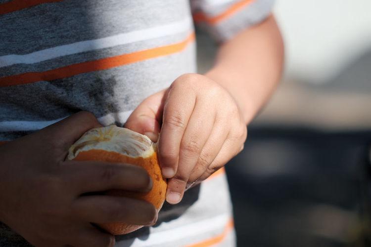 Close-Up Of Boy Peeling Orange